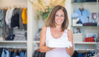 Beautiful middle age hispanic woman standing with smile on face at clothes store. Shop owner and shop assistant smiling confident and cheerful holding clothes..