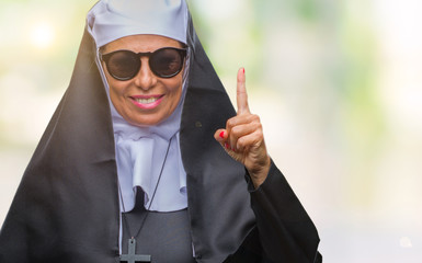 Middle age senior catholic nun woman wearing sunglasses over isolated background pointing finger up with successful idea. Exited and happy. Number one.
