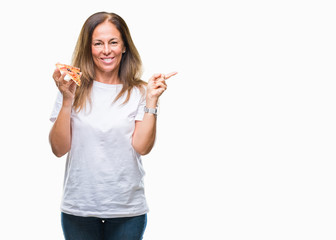 Middle age hispanic woman eating pizza slice over isolated background very happy pointing with hand and finger to the side