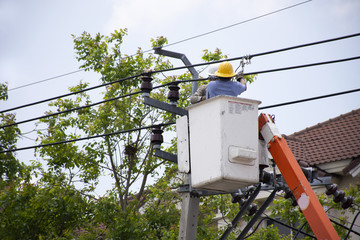 Electrician worker of Metropolitan Electricity Authority working repair electrical system on electricity pillar or Utility pole in Bangkok, Thailand
