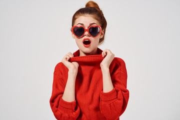 surprised woman in glasses holding a sweater collar