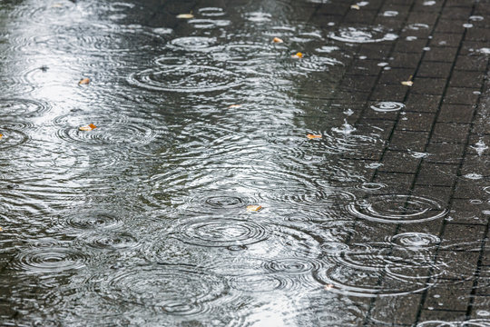 city sidewalk with big water puddles during heavy rain closeup view