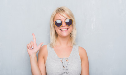 Adult caucasian woman over grunge grey wall wearing retro sunglasses surprised with an idea or question pointing finger with happy face, number one