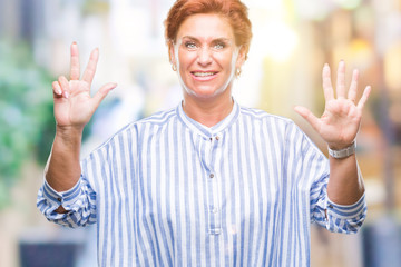 Atrractive senior caucasian redhead woman over isolated background showing and pointing up with fingers number eight while smiling confident and happy.