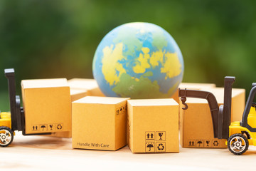 Mini forklift truck load cardboard box on wooden table with nature background. The globe is surrounded by boxes. Logistics and transportation management ideas and Industry business commercial concept.