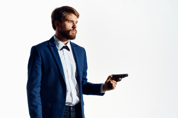 a man in a suit holds a gun in his hand