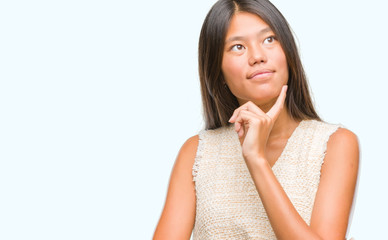 Young asian woman over isolated background with hand on chin thinking about question, pensive expression. Smiling with thoughtful face. Doubt concept.