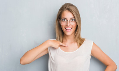 Beautiful young woman standing over grunge grey wall wearing glasses with surprise face pointing finger to himself