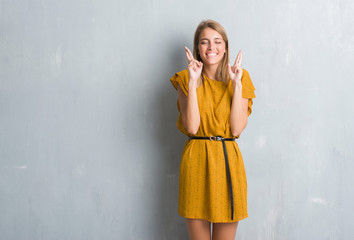 Beautiful young woman standing over grunge grey wall wearing a dress smiling crossing fingers with hope and eyes closed. Luck and superstitious concept.