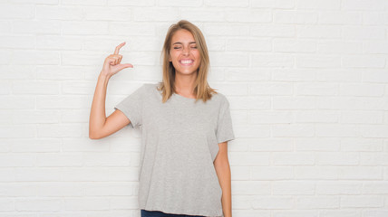 Beautiful young woman over white brick wall smiling and confident gesturing with hand doing size...