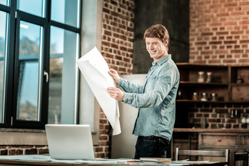 Skillful engineer. Cheerful nice delighted man holding a blueprint and smiling while working alone in the office