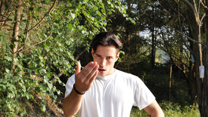 Young handsome man standing in nature, saying Come Here or Come Closer with hand gesturing