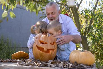 Grandfather carving pumpkins with grandchildren for Halloween
