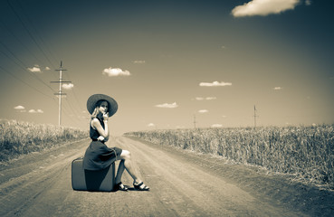 young girl in a blue dress and a hat with a suitcase on the rural road