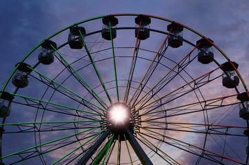 Ferris wheel carousel against the background of the setting sun
