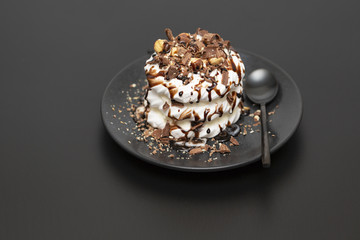 Meringue dessert with chocolate sauce, chocolate, nuts and cream.