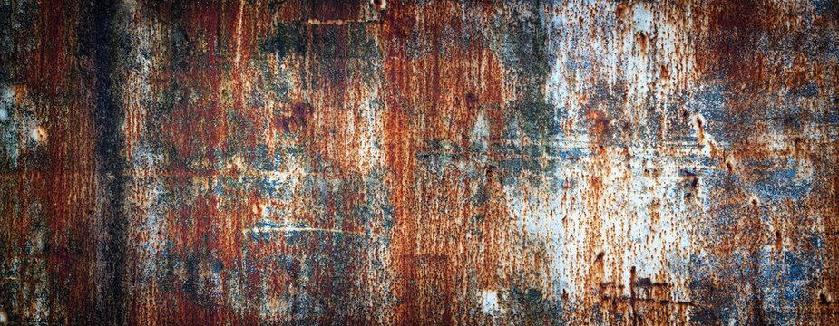 Rusty metal wall, old sheet of iron covered with rust with multi-colored paint