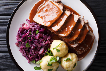 Traditional Sauerbraten dish with potato dumplings and red cabbage close-up. German cuisine. horizontal top view