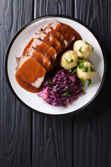 Festive German full dinner Sauerbraten - beef stew with gravy served with potato dumplings and red cabbage close-up. Vertical top view