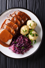 Traditional Sauerbraten dish with potato dumplings and red cabbage close-up. German cuisine. Vertical top view