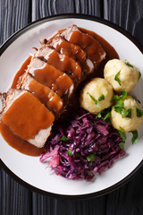 German roast pot Sauerbraten served with potato dumplings and red cabbage close-up. Vertical top view