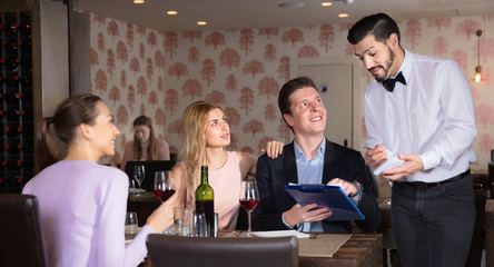 Handsome waiter taking order from young people in restaurant