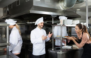 Chef of restaurant with team of cooks preparing food