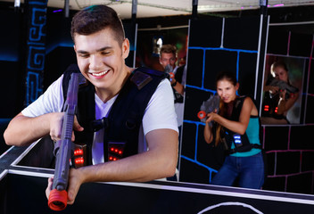 Portrait of excited guy with laser pistol playing laser tag in arena