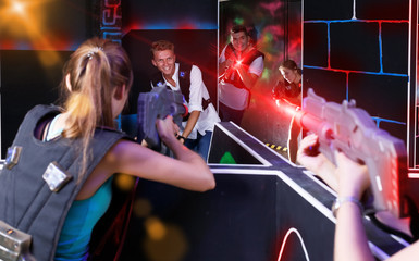 Teams of laser tag game girls and guys playing emotionally oppos