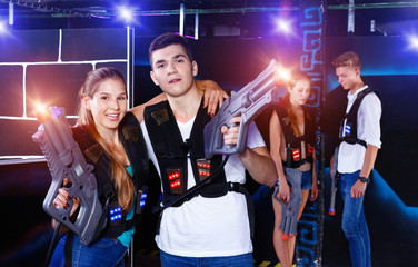 Young guys and girls in vests holding plasticlaser pistols and p
