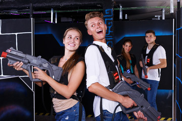 Guy and girl are happy with their victory in laser tag game