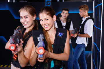 Two smiling girls posing with plastic laser pistols and two guys in background in laser tag room