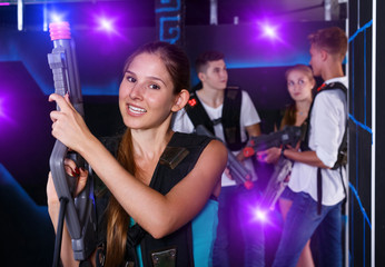 Positive girl holding laser pistol during playing lasertag game
