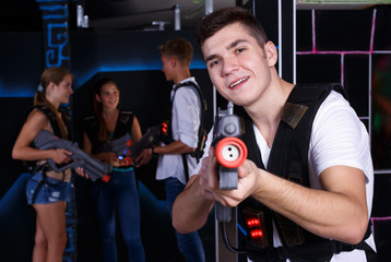 Excited  guy with laser pistol while playing lasertag with his friends