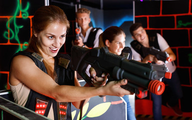 Portrait of exciting girl with laser pistol playing laser tag in dark room