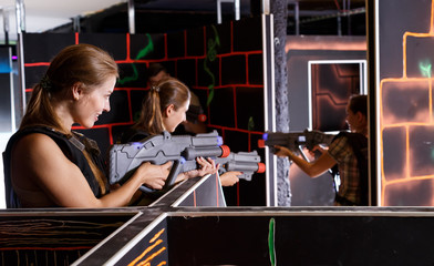 Guys and girls in vests and with laser pistols playing lasertag game in labyrinth