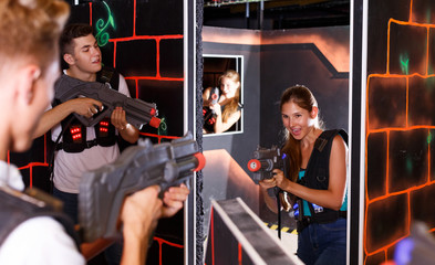 Excited people playing enthusiastically laser tag game