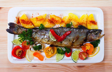 Picture of  tasty baked whole  trout  with potatoes, greens and tomatoes