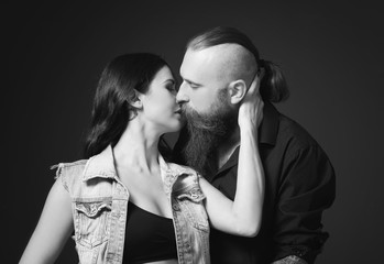 Tattooed man kissing his girlfriend on dark background, black and white effect