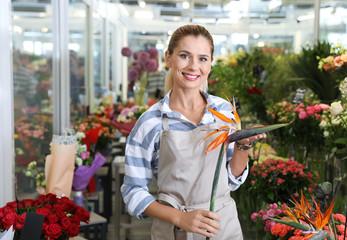 Beautiful female florist working in flower shop