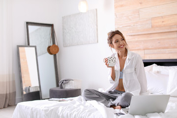 Young happy woman with cup of aromatic coffee on bed at home. Lazy morning