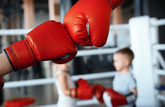 Little kid with trainer in boxing gloves on ring