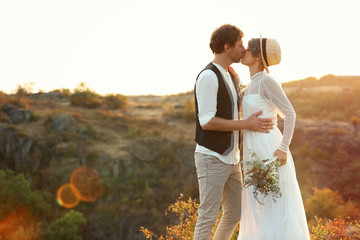 Happy newlyweds with beautiful field bouquet kissing outdoors