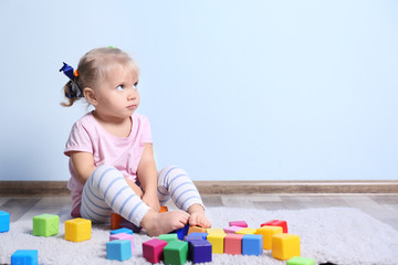 Adorable little girl playing with blocks indoors