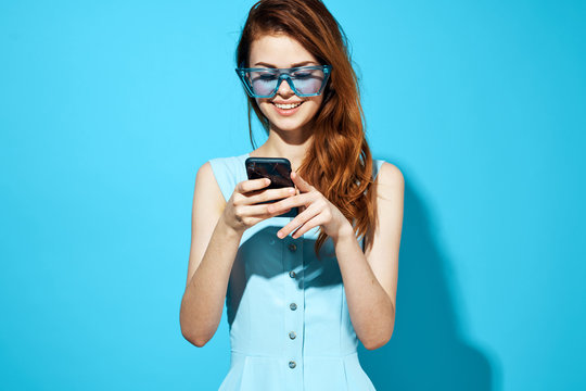 woman in blue glasses and dress is looking at the phone