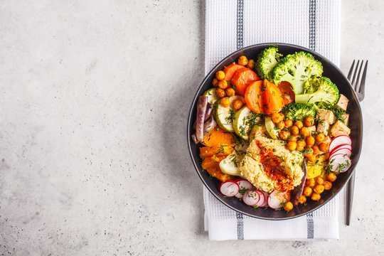 Vegan Buddha bowl with baked vegetables, chickpeas, hummus and tofu, top view.