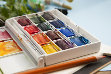 Pallette of watercolor paints and paintbrushes for painting. Blue background. Selective focus.
