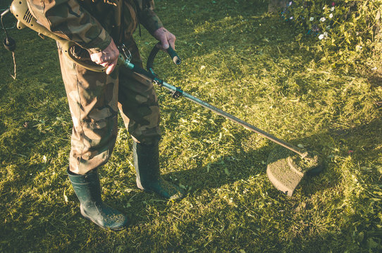 Man in protective camouflage mowing grass with string electric trimmer