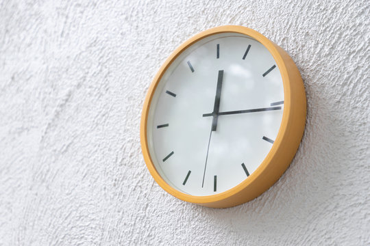 yellow clock on concrete wall show time  on mid day.