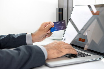 Hand of  businessman holding credit card making payment transaction online with laptop computer in office